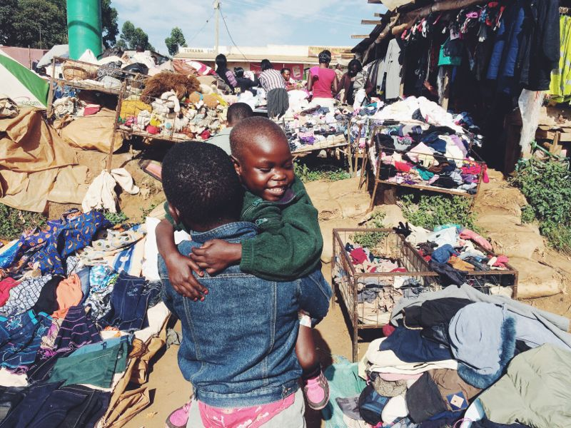 Pascal carrying Gracie to the outdoor market to shop for some new clothes.